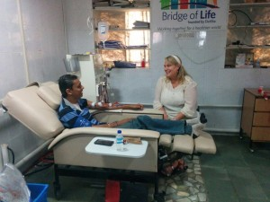 Lori visits with a dialysis patient at a clinic Bridge of Life helped to establish in India